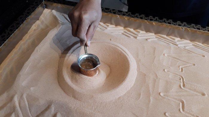 Pelayan sedang memutar-mutar gelas tembaga berisi kopi di atas pasir panas pada Jumat (8/1/2021).