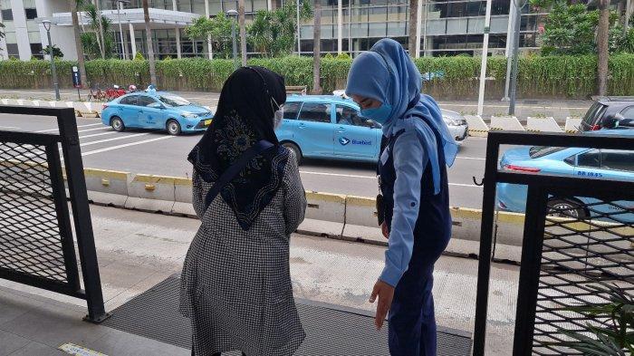 Krisni Haerani mengarahkan seorang penumpang berdiri di batas aman sebelum naik bus TransJakarta di halte Bundaran HI, Jakarta Pusat, Rabu (15/9/2021).