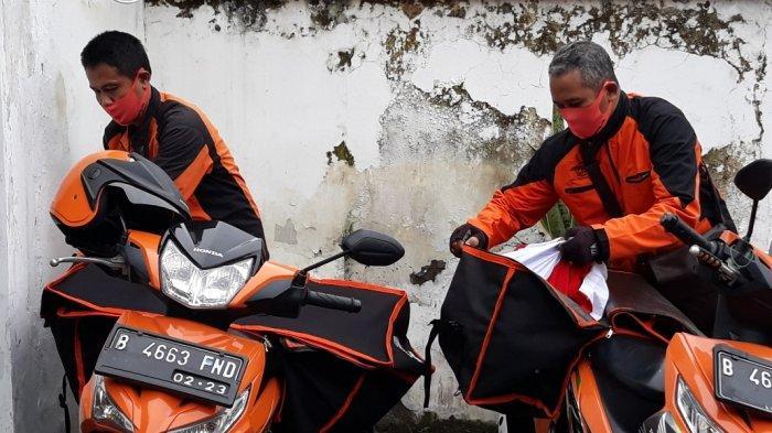 Kurir PT Pos Indonesia yang bertugas mengantar paket sembako dari pemerintah pusat ke warga di Pulogadung, Jakarta Timur, Jumat (24/4/2020).