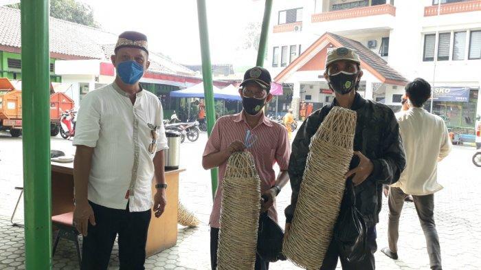 Lurah Ciracas Rikia Marwan (baju putih) saat penyerahan bongsang untuk wadah distribusi daging hewan kurban Iduladha 1442 Hijriah di Ciracas, Jakarta Timur, Selasa (20/7/2021).