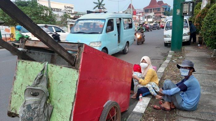 Tatang bersama istri dan anaknya menjelang buka puasa saat ditemui di Jalan Raya Jatiwaringin, Pondok Gede, Kota Bekasi, Rabu (29/4/2020)