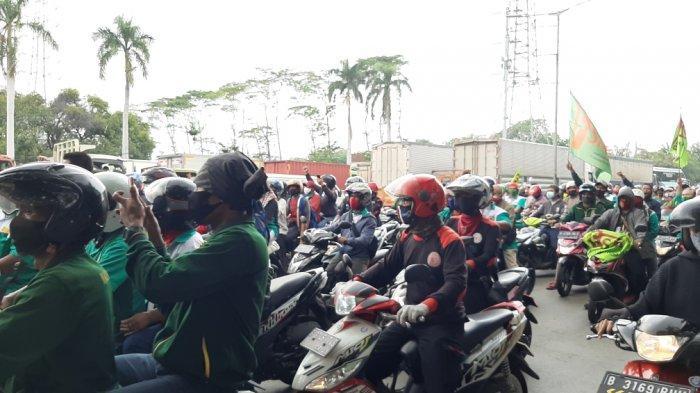 Massa buruh melintas di Jalan Raya Bekasi, Cakung, Jakarta Timur, Kamis (8/10/2020).