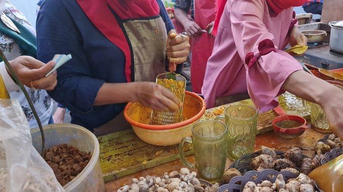 Memarut bahan dasar untuk minuman jamu Bang Adut di Pasar Lama Tangerang, pada Kamis (23/9/2021).
