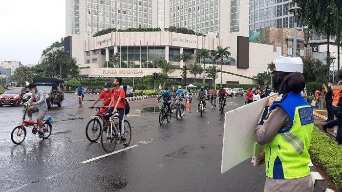 Diguyur Hujan Deras Sejak Pagi, Begini Suasana Warga Bersepeda di Bundaran HI
