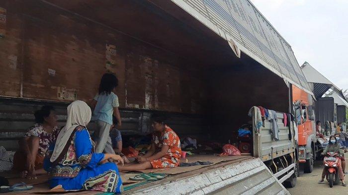 Warga korban banjir di Kampung Bojong, Desa Bojong Sari, Kecamatan Kedungwaringin, Kabupaten Bekasi terpaksa mengungsi di truk kontainer, Senin (22/2/2021).