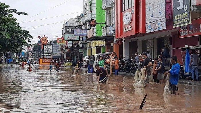 Keseruan Warga Menjala Ikan di Tengah Banjir Jalan Raya Bintara Bekasi
