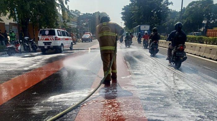 Personel Damkar Jakarta Timur saat proses penanganan tumpahan minyak goreng di Jalan Pemuda, Pulogadung, Rabu (17/3/2021).