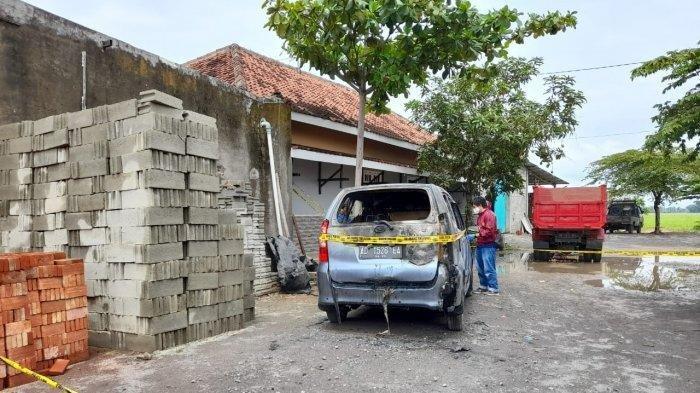 Personel kepolisian memasang garis polisi di mobil Daihatsu Xenioa berplat nomor polisi AD-1526-EA, Desa Sugihan. Kecamatan Bendosari, Kabupaten Sukoharjo, Rabu (21/10/2020).