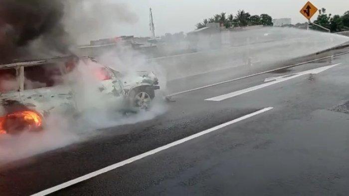 Personel Damkar Jakarta Timur saat proses pemadaman api mobil Nissan X-Trail yang terbakar di Tol Becakayu, Sabtu (9/1/2021)