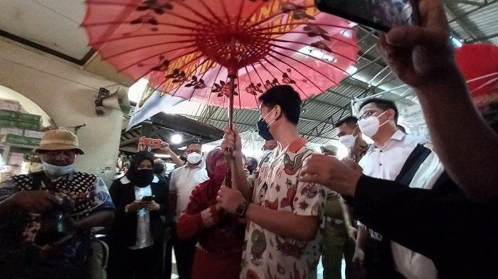 Momen Suharni memayungi Gibran dan memberikan payung tersebut pada Wali Kota Solo di Pasar Gede, Jumat (26/2/2021).