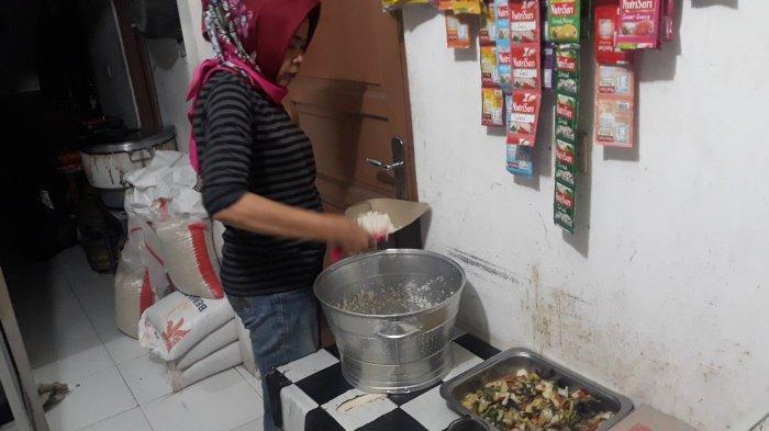 Nafsiah sedang menciduk nasi dari panci di dalam warung bolong. Dulu ini ruangan merupakan kamar tidurnya yang berdekatan dengan proyek pembangunan mal Kemang Village pada Senin (9/11/2020).