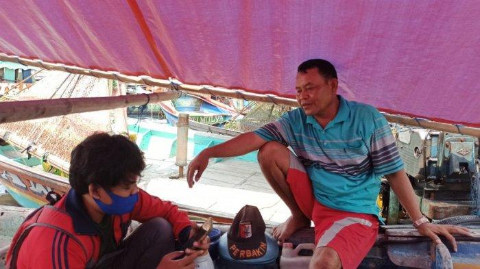 Kurdianto (kanan), salah seorang nelayan Cilincing, menceritakan pengalaman mudik menggunakan perahu.