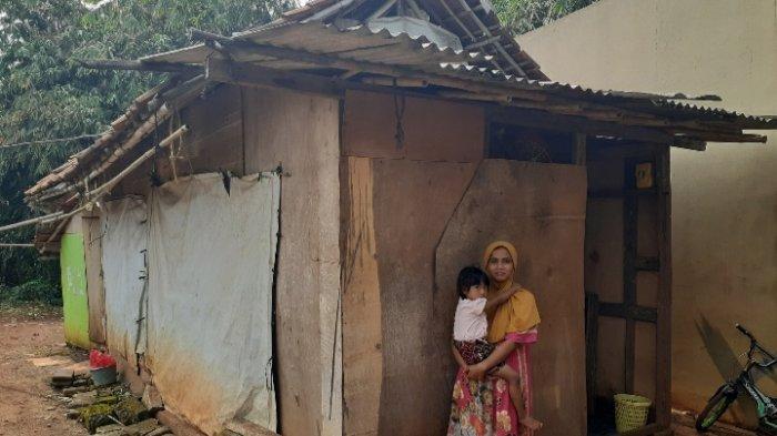 Nuraini bersama cucu di depan rumah reyotnya