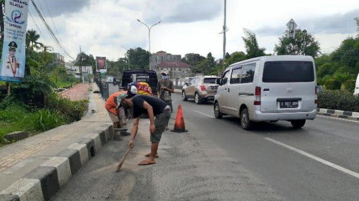 Sejumlah pekerja dari Dinas Pekerjaan Umum Tangsel terlihat sedang membersihkan pasir dan kerikil di Jalan Raya Ciater, Serpong, Jumat (11/12/2020).