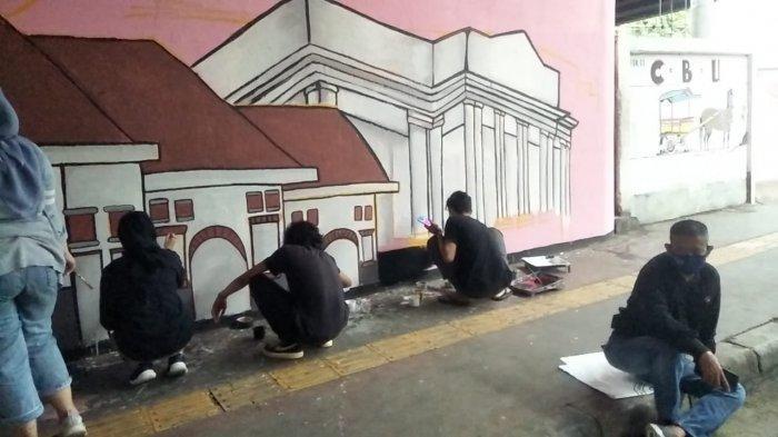 Personel PPSU Kelurahan Rawa Bunga dan seniman UNJ saat proses pembuatan mural di Jalan Jatinegara Barat dan Kolong Viaduct, Jatinegara, Jakarta Timur, Selasa (15/12/2020)