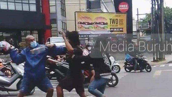 Tangkapan layar video saat dua pria diduga pengamen jalanan dengan seorang pengendara motor berkelahi di perempatan kawasan Buaran, Duren Sawit, Jakarta Timur, Kamis (11/2/2021).