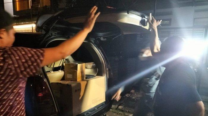 Petugas membawa satu kardus berukuran besar dan barang lainnya setelah menggeledah rumah di Komplek Taman Villa Mulia, Kembangan, Jakarta Barat, Jumat (27/8/2021) malam.