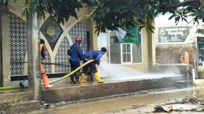 Petugas gabungan bantu bersihkan lumpur pascabanjir di RW 3 dan RW 4 Kelurahan Cipinang Melayu, Makasar, Jakarta Timur, Senin (22/2/2021)