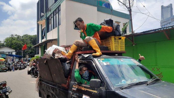 Petugas membantu proses bersih-bersih pemukiman warga di Kelurahan Kuningan Barat, Minggu (21/2/2021).