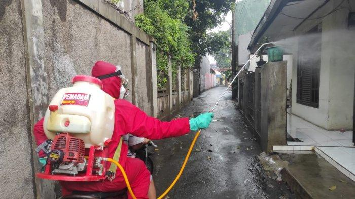 Personel Damkar Jakarta Timur saat melakukan proses penyemprotan disinfektan di permukiman warga, Minggu (31/1/2021).