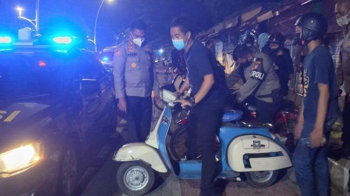 Petugas gabungan mengamankan motor Vespa milik anak muda dalam razia di kawasan Barito, Kebayoran Baru, Jakarta Selatan, Minggu (12/9/2021) dini hari.