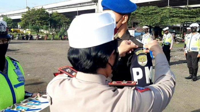 Operasi Keselamatan Jaya 2021 di kawasan Cawang, Jakarta Timur. Petugas membagikan brosur terkait tujuan kegiatan ini kepada pengendara, Senin (12/4/2021).