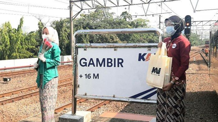 Petugas memberikan bunga mawar kepada penumpang kereta di rangkaian kereta api, Stasiun Gambir, Jakarta Pusat, Rabu (21/4/2021).
