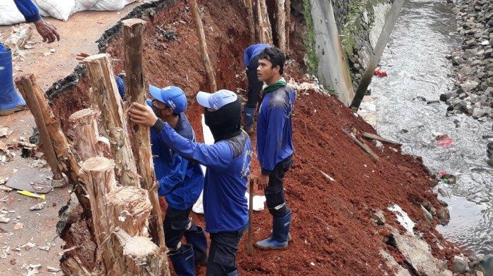 Personel Sudin SDA Satpel Kecamatan Kramat Jati saat proses penanganan turap saluran PHB Kali Induk yang longsor, Senin (22/2/2021).