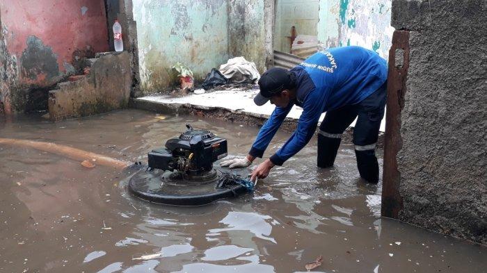 Personel Sudin Sumber Daya Air (SDA) Jakarta Timur saat menyedot debit air dari permukiman warga Kelurahan Cipinang Melayu menggunakan pompa portabel, Makasar, Sabtu (24/7/2021).