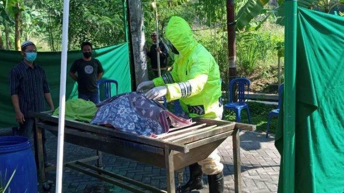 Anggota Polisi Sat Samapta Polrestabes Semarang, Aiptu Andi Surwano menggunakan alat seadanya untuk memandikan jenazah terpapar covid 19 di Perum Graha Sendangmulyo Tembalang
