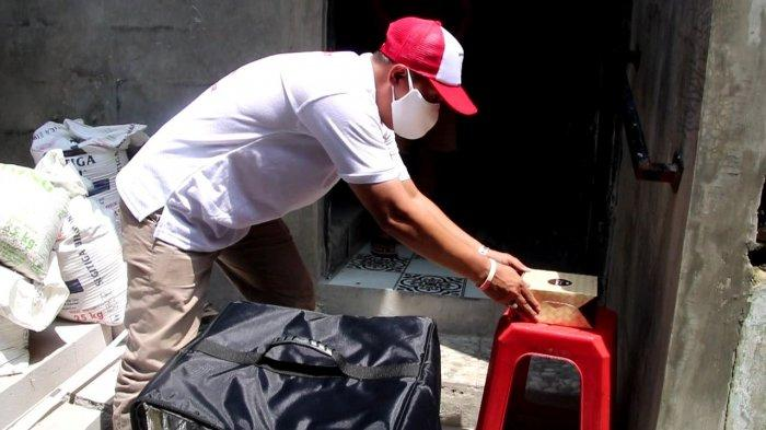 Seorang Delivery Isoman ini mengantarkan makanan ke pasien Covid-19 yang isolasi mandiri, di wilayah Kecamatan Sawah Besar, Jakarta Pusat, Rabu (27/1/2021).