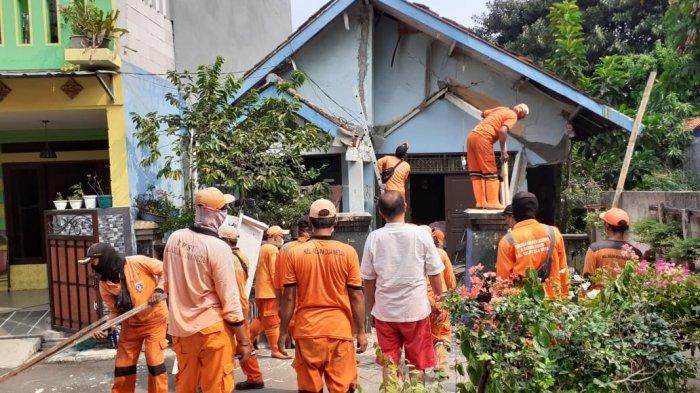 Personel PPSU Kelurahan Kelapa Dua Wetan yang bagian atap teras rumahnya longsor di Ciracas, Jakarta Timur, Senin (2/8/2021)