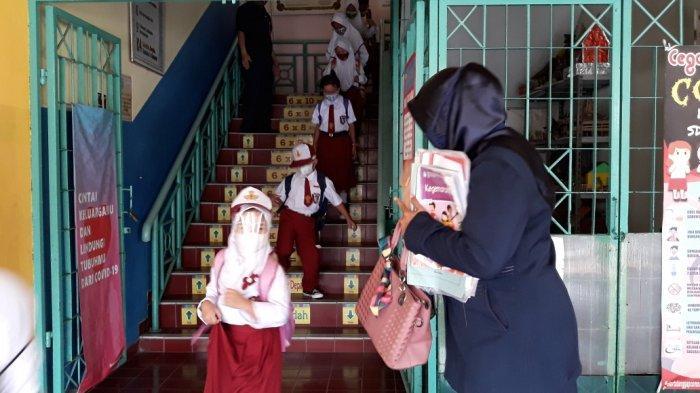 Murid SDN Kelapa Dua Wetan 02 usai mengikuti pembelajaran tatap muka (PTM) terbatas di Ciracas, Jakarta Timur, Senin (30/8/2021).