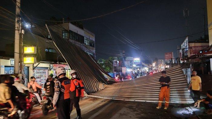 Rangka atap baja ringan yang terbang dan jatuh menutup Jalan Raya Sawangan akibat diterpa puting beliung, Selasa (21/9/2021).