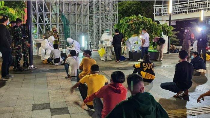 Puluhan remaja nongkrong di Spot Taman Budaya, Dukuh Atas, yang terjaring razia Satpol PP dan TNI-Polri langsung diminta menjalani rapid test antigen, Minggu (20/12/2020) dini hari WIB.