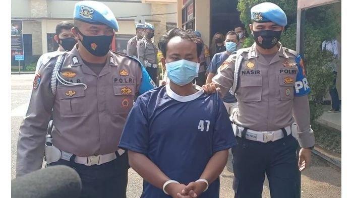 RI (33), suami yang tega memukul dan menusuk istri sendiri, RM (25), saat digiring polisi di Mapolresta Bandung, Senin ( 3/5/2021).