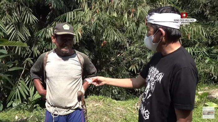 Kang Dedi memberikan uang kepada Sersan, pria tua pencari picung yang alami gangguan pendengaran.