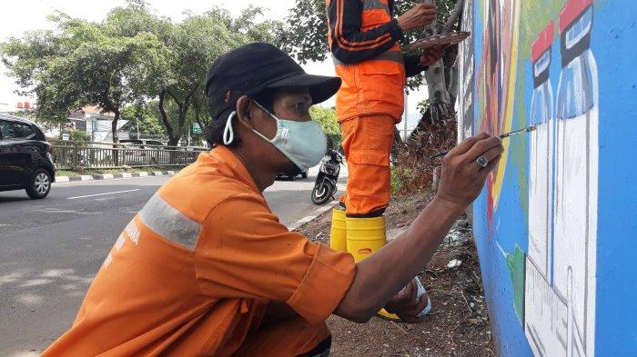 Petugas PPSU Bukit Duri, Rokib (jongkok) sedang membantu Edi melukis di dinding Jalan KH Abdullah Syafei, Tebet, Jakarta Selatan pada Selasa (4/5/2021).
