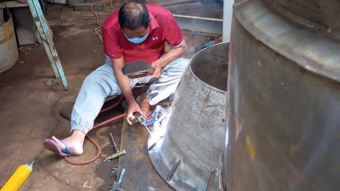 Rudy saat mengelas tandon air di bengkelnya di kawasan Puncangsawit pada Kamis (18/2/2021)