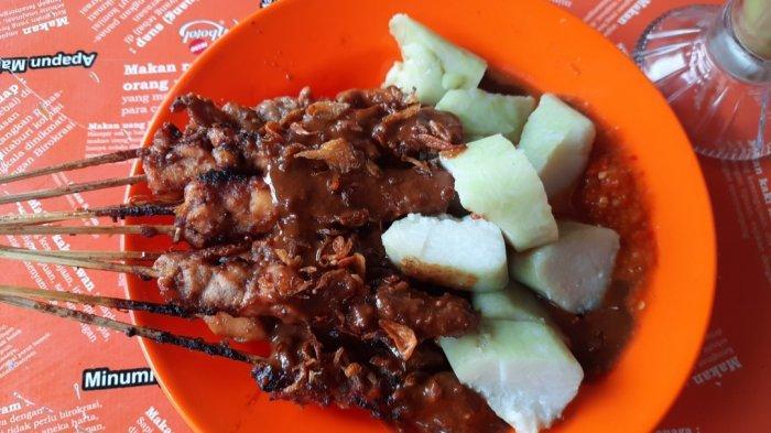 Sepiring sate ayam disajikan lengkap dengan sambal dan taburan bawang goreng di atasnya.