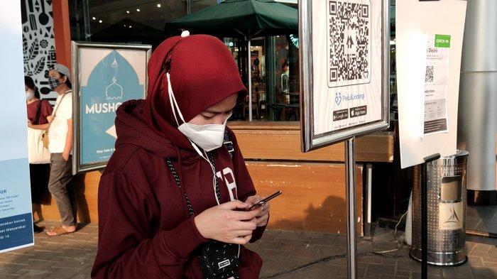 Pengunjung melakukan scan barcode aplikasi PeduliLindungi sebelum memasuki Margo City Mall, Rabu (18/8/2021).