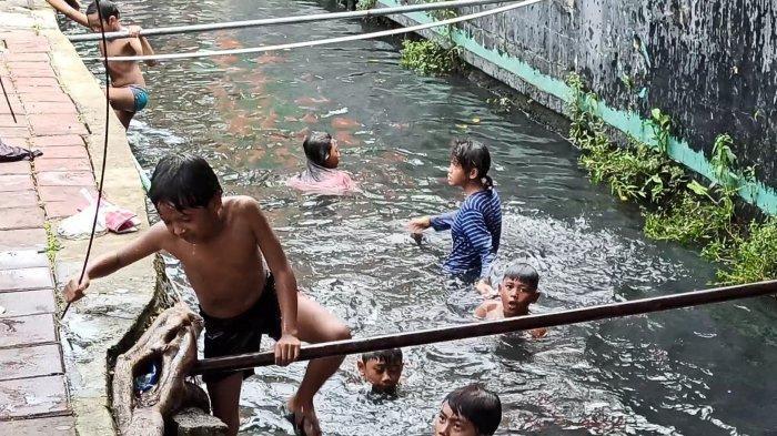 Selokan di Jalan Mangga Dua Raya, tepatnya depan kawasan Ruko Grand Boutique Mangga Dua, Pademangan, Jakarta Utara, menjadi tempat anak-anak bermain dan berenang, Kamis (4/4/2021).