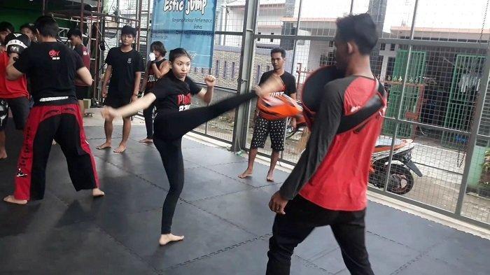 Seorang anggota perempuan berlatih menendang di ruang studio Piranha Stunt Indonesia pada Kamis (8/4/2021).