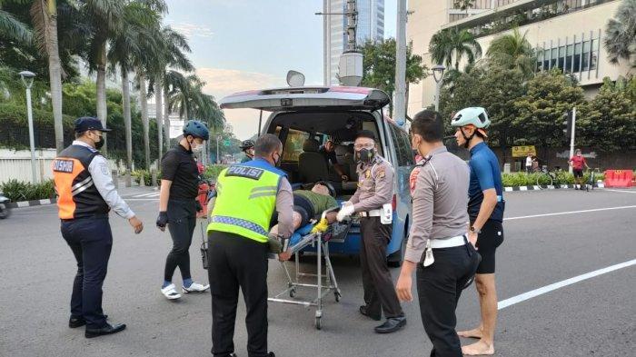 Petugas keamanan menolong pesepeda yang menjadi korban tabrak lari, di Bundaran Hotel Indonesia, Jalan MH Thamrin, Jakarta Pusat, Jumat (12/3/2021) pagi.