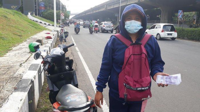 Serli (37) sedang memegang uang pecahan baru di tepi Jalan TB Simatupang, Cilandak Barat, Cilandak, Jakarta Selatan pada Selasa (11/5/2021).
