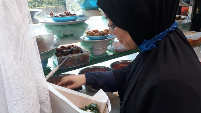 Shiwy sedang menyiapkan nasi padang untuk dibagikan secara gratis bagi warga yang melintas pada Jumat (7/5/2021).