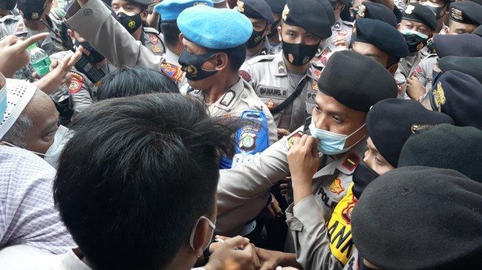 Anggota tim kuasa hukum dan simpatisan Rizieq Shihab saat terlibat aksi saling dorong dengan anggota Polri depan gerbang Pengadilan Negeri Jakarta Timur, Jumat (19/3/2021).