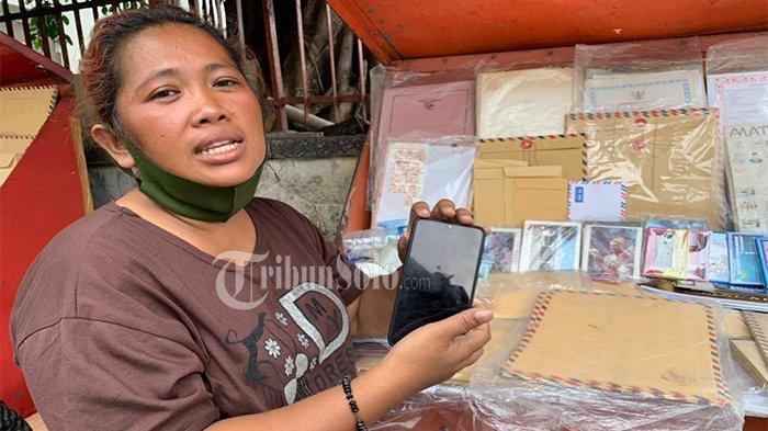 Sosok yang menemukan uang belasan juta rupiah Desi Natalia (42) saat berjualan amplop hingga prangko di kawasan Kantor Pos Solo, Jalan Jenderal Sudirman, Jumat (7/5/2021).