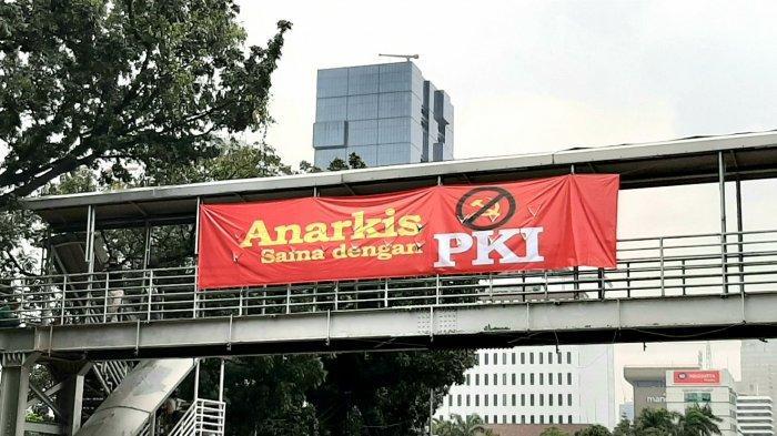 Spanduk Bertuliskan 'Anarkis Sama dengan PKI' Terbentang di JPO Jalan Medan Merdeka Barat