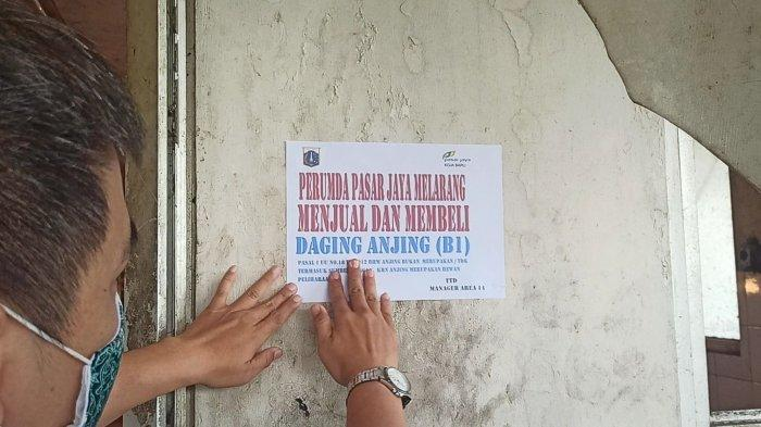 Pengelola Pasar Koja Baru, Koja, Jakarta Utara, menempelkan stiker larangan jual-beli daging anjing, Senin (13/9/2021).